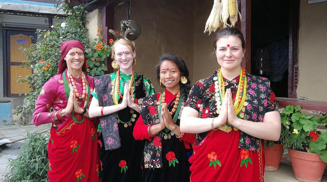Projects Abroad volunteers and their host family dressed in bright, traditional Nepali clothes